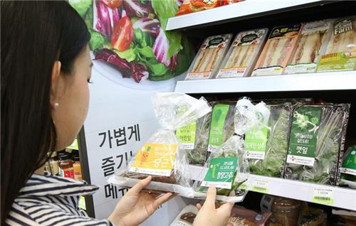 A woman buys groceries at a convenience store.