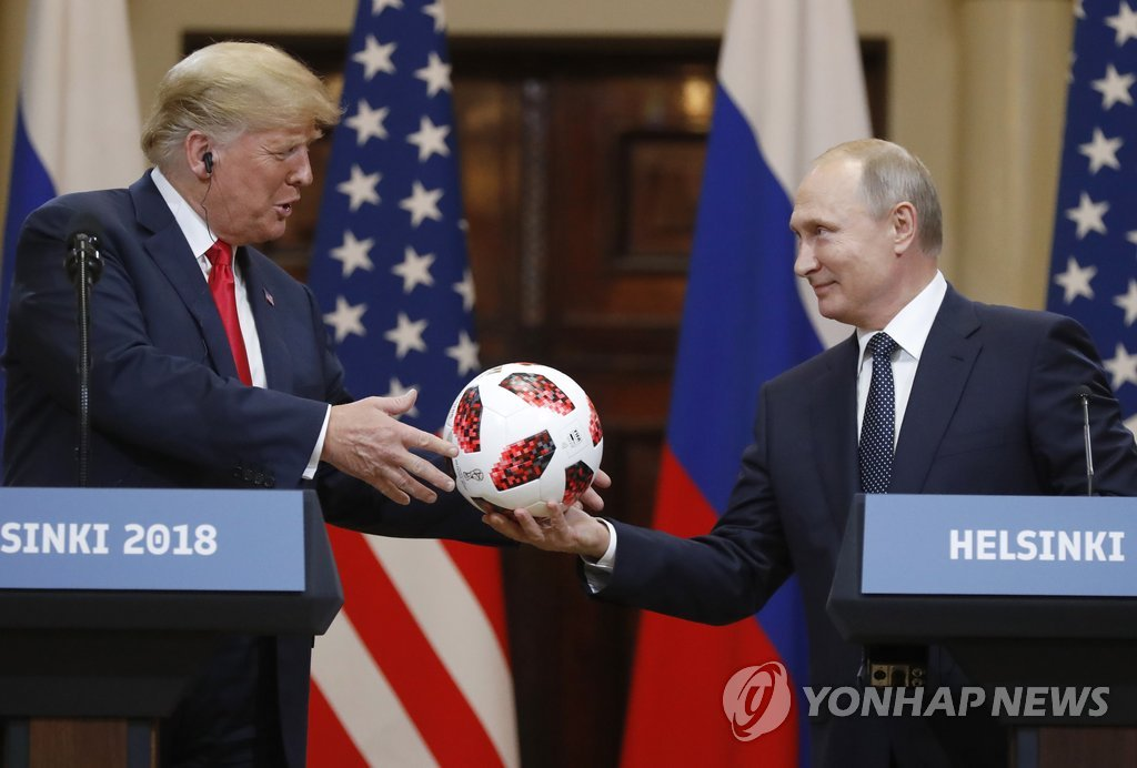 U.S. President Trump (L) receives an official Russia World Cup ball from Russian President Vladimir Putin.