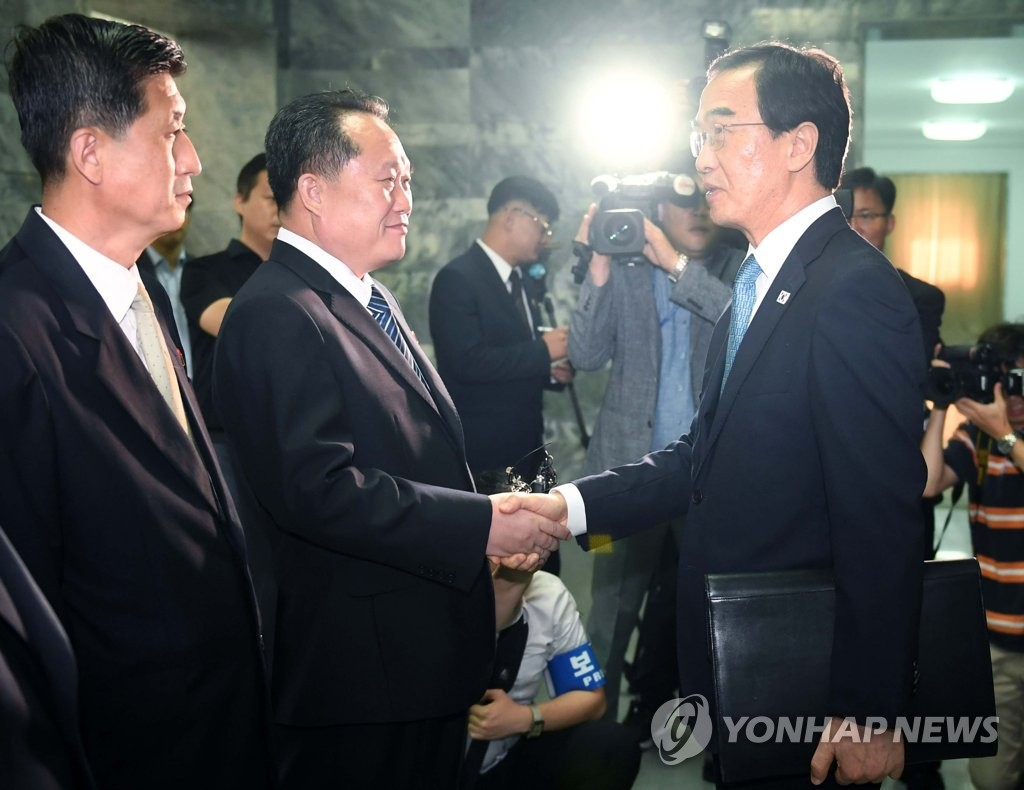 Unification Minister Cho Myoung-gyon (R) shakes hands with Ri Son-gwon, the chairman of North Korea's Committee for Peaceful Reunification