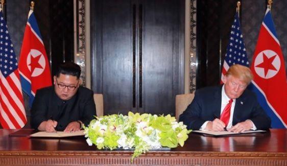 공동성명에 서명하는 김정은 위원장과 트럼프 대통령 <사진=연합>