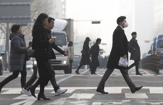 Citizens cross a road in downtown Seoul on Feb. 22, 2019, as South Korea took emergency measures to cut fine dust nationwide, except Jeju Island, with chocking particulate matter gripping most of the country for a third day.<Photo: Yonhap News>