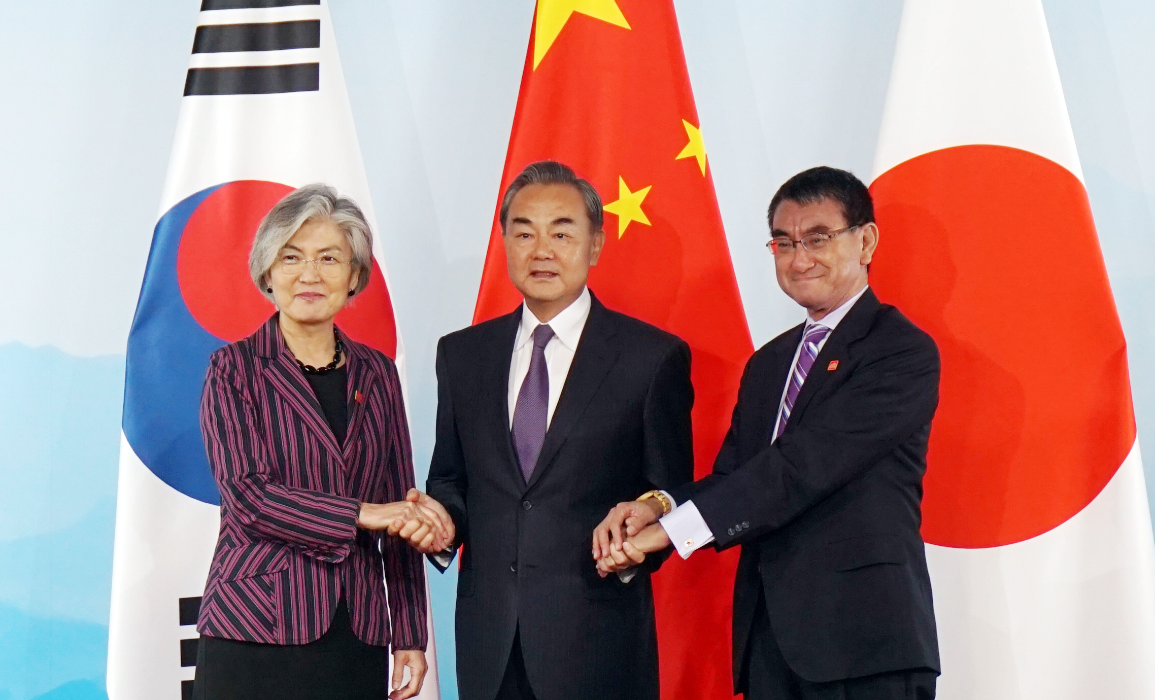 South Korean Foreign Minister Kang Kyung-wha (L), Chinese Foreign Minister Wang Yi (C) and Japanese Foreign Minister Taro Kono (R) hold hands ahead of the ninth trilateral foreign ministers' meeting in Beijing, China on August 21, 2019. <Photo: Yonhap News>