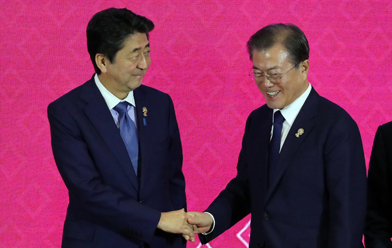 Japanese Prime Minister Shinzo Abe (L) and South Korean President Moon Jae-in meet in early November in Bangkok.