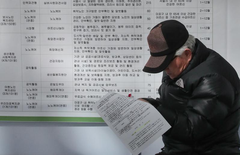 An elderly man reads a job ad.