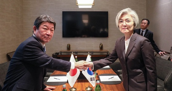Foreign Minister Kang Kyung-wha (R) shakes hands with her Japanese counterpart, Toshimitsu Motegi