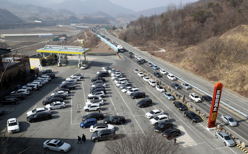 A rest area along an expressway is heavily crowded.