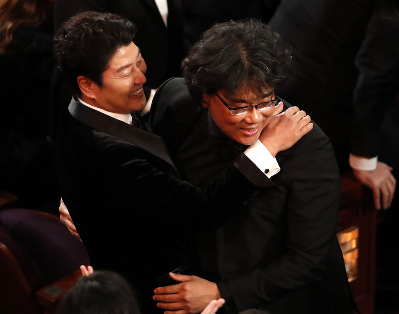 """Actor Song Kang-ho (L) embraces director Bong Joon-ho after """"Parasite"""" wins Best Picture at the Oscars"""
