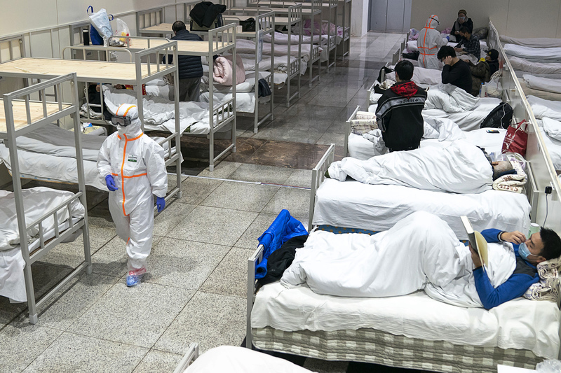 medics in Wuhan pass by patients lying in a makeshift hospital in a building that formally served as a large exhibition center