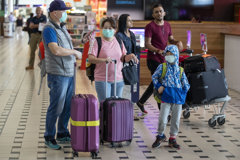 Tourists at the Brisbane Airport wearing masks