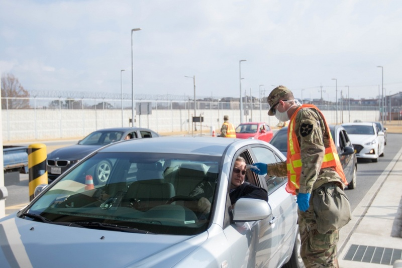 A U.S. military official takes the temperature of a driver entering Camp Humphreys