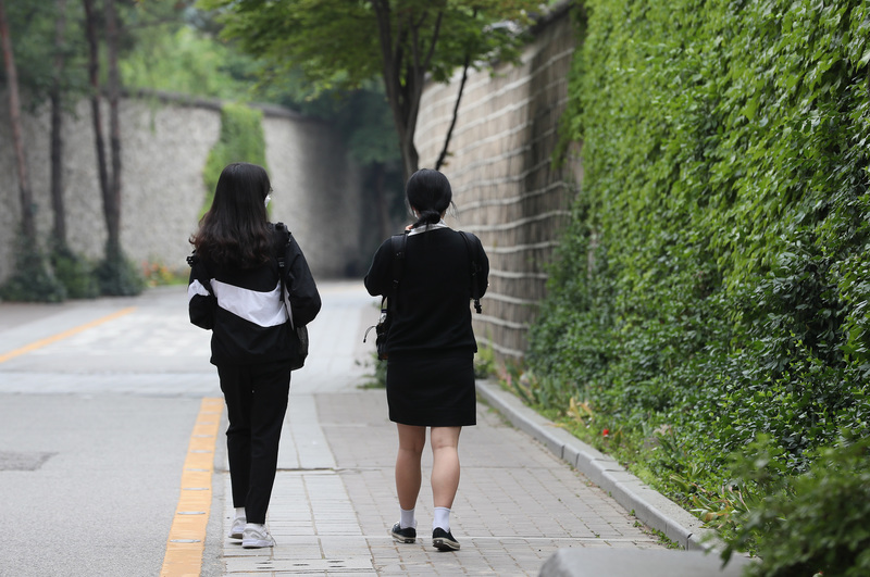 Two young students walk to their school in Seoul.