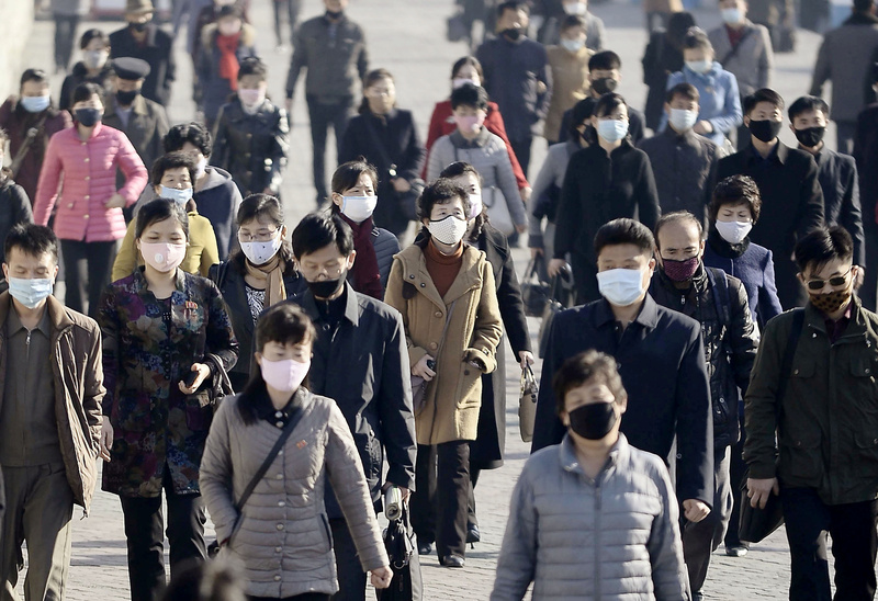 North Koreans wear masks while walking down a street in the capital Pyongyang.
