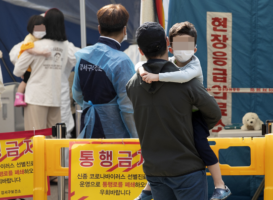 Parents and children wait outside a COVID-19 testing facility in Seoul's Gangseo District after a local 6-year-old boy tested positive for the virus.