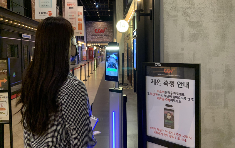 A woman gets her face scanned and temperature checked by CGV's Smart Pass system.