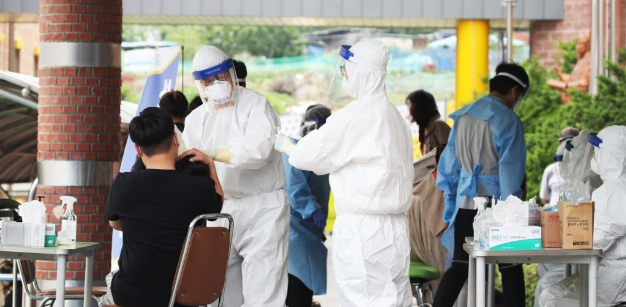 Local residents in the city of Anyang in Gyeonggi Province receive help at a coronavirus testing center.