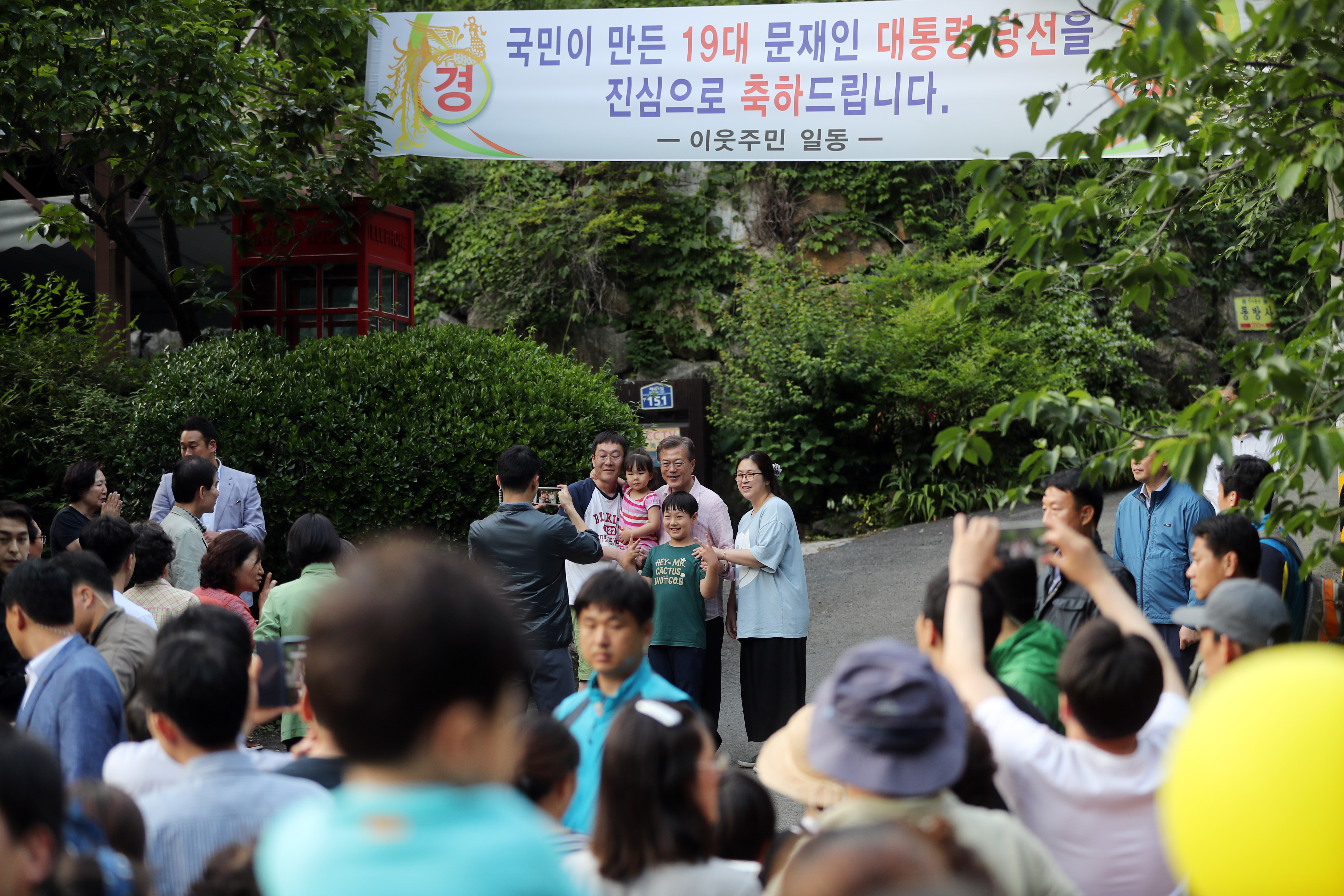 President Moon Jae-in takes a photo with residents in front of his private home in Yangsan, South Gyeongsang Province.