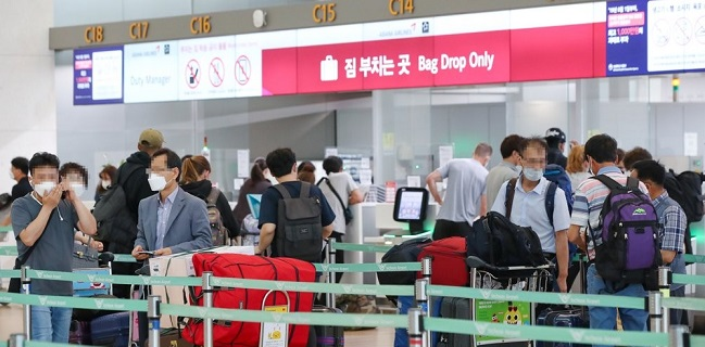 Travelers wait in line to go through procedures for departure at Incheon International Airport.
