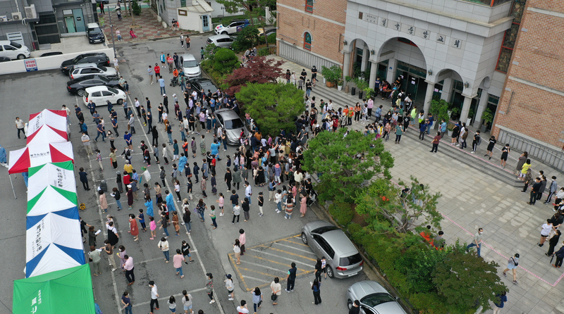 Residents of Gwangju flock to a COVID-19 testing center amid a spike in local cluster infections.