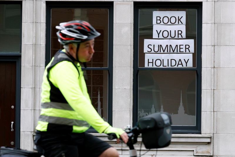A man rides a bicycle past a travel agents store, amid the coronavirus outbreak, in Manchester, Britain.