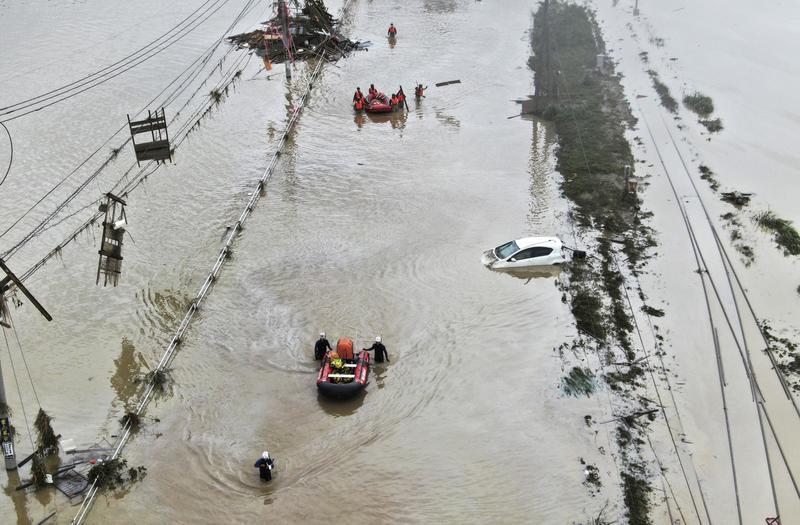 Rescue workers aid residents by boat following heavy rain in Kumamura, Kumamoto Prefecture, southern Japan on July 5, 2020.