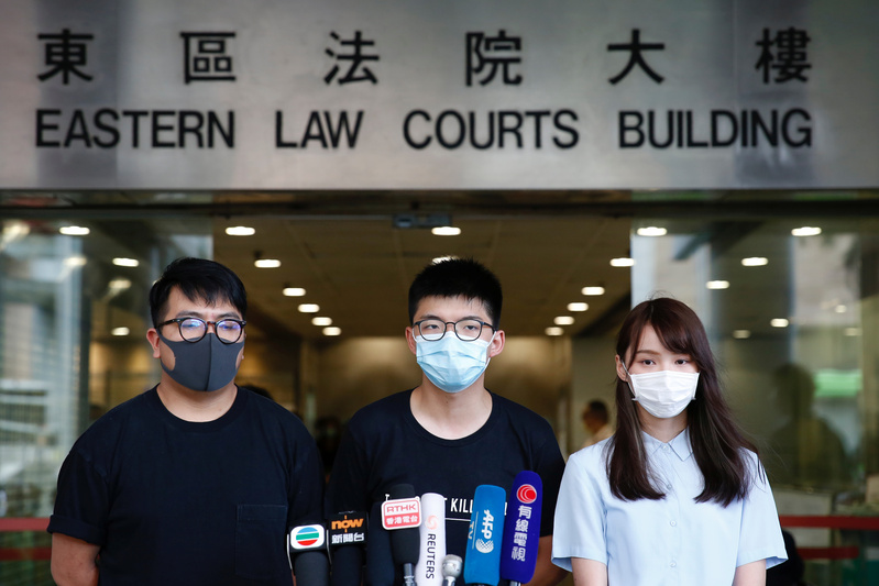Pro-democracy activists Ivan Lam (L), Joshua Wong (C) and Agnes Chow (R) stand outside the Eastern Court in Hong Kong on July 6, 2020.