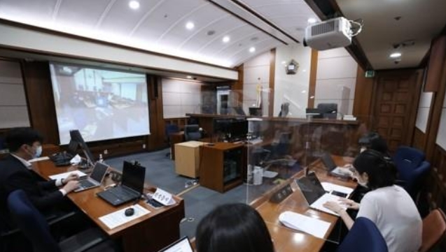 Reporters in Seoul watch the hearing on the extradition case of Son Jung-woo, the operator of one of the world's biggest child porn sites.