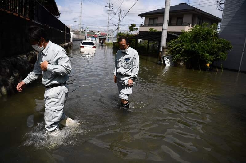 People wade through flood waters in Kurume in Kumamoto Prefecture, Japan on July 8, 2020.
