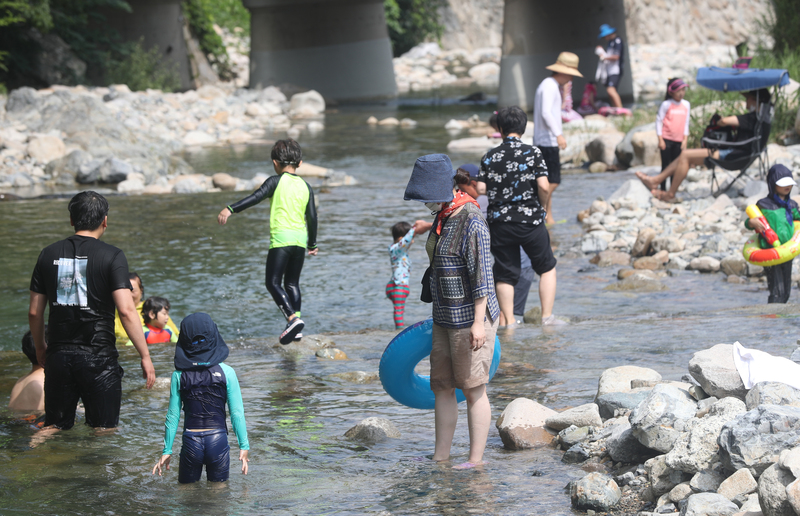 Children and adults cool off while wading in a stream at Jangyudaecheong Valley in Gimhae, South Gyeongsang Province.