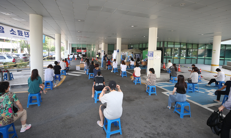 Gwangju residents keep social distance while waiting to receive help at a COVID-19 screening clinic.