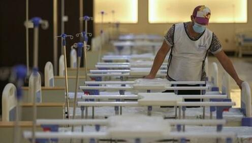 A worker prepares beds at a makeshift hospital in Baghdad, Iraq.