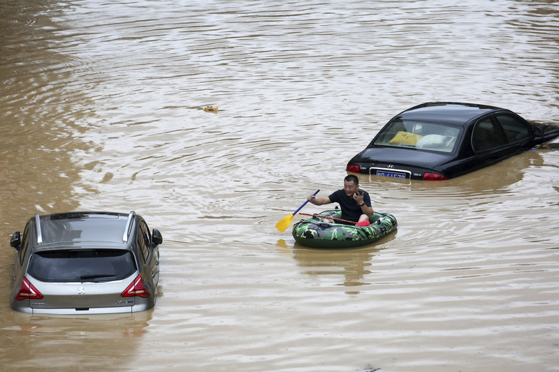 A man in an inflatable boat paddles past submerged cars during a flood in Rongshui County in China's Guangxi Zhuang Autonomous Region.