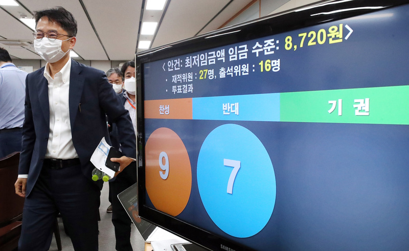 Minimum Wage Commission chairman Park Jun-sik walks past a screen showing the final vote on a proposal to increase next year's hourly wage to 8,720 won.