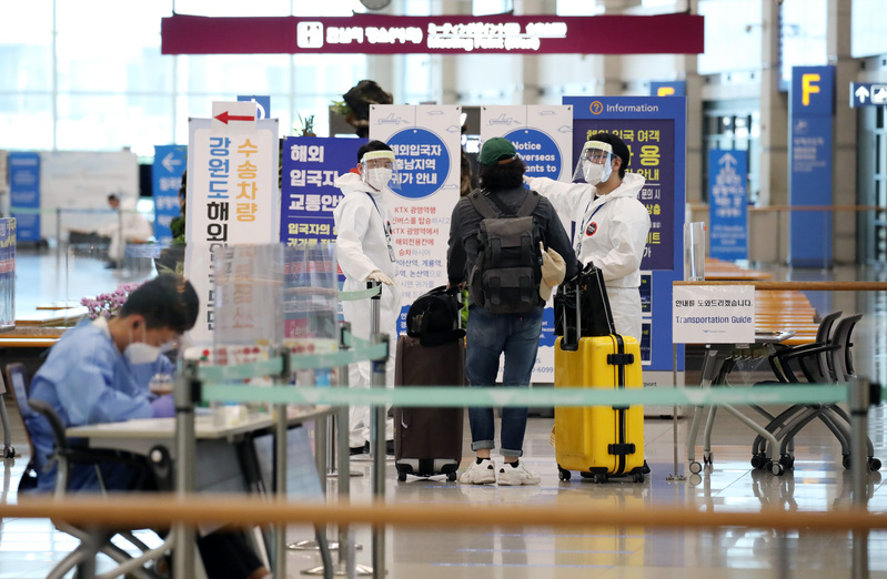 Medical workers help an arriving traveler through quarantine procedures at Incheon International Airport.