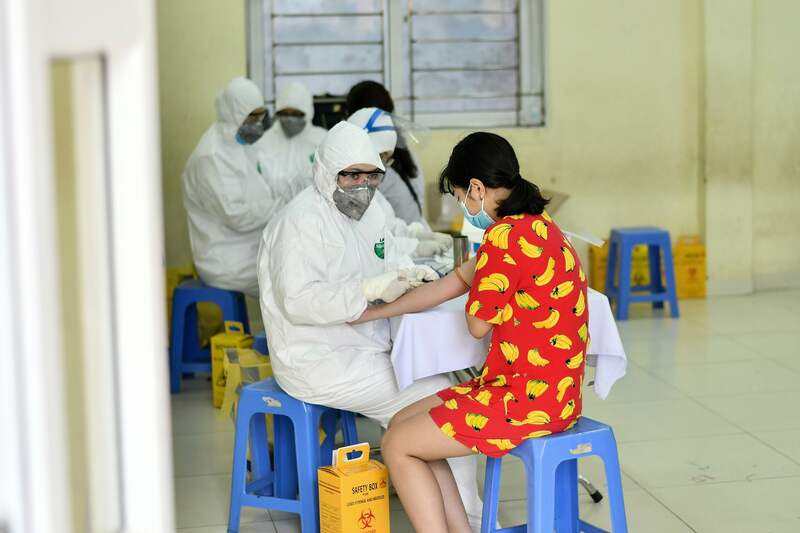 Health workers collect a blood sample of a resident at a makeshift rapid testing center as Vietnam records a rise in cases of COVID-19 in Hanoi on July 31, 2020.