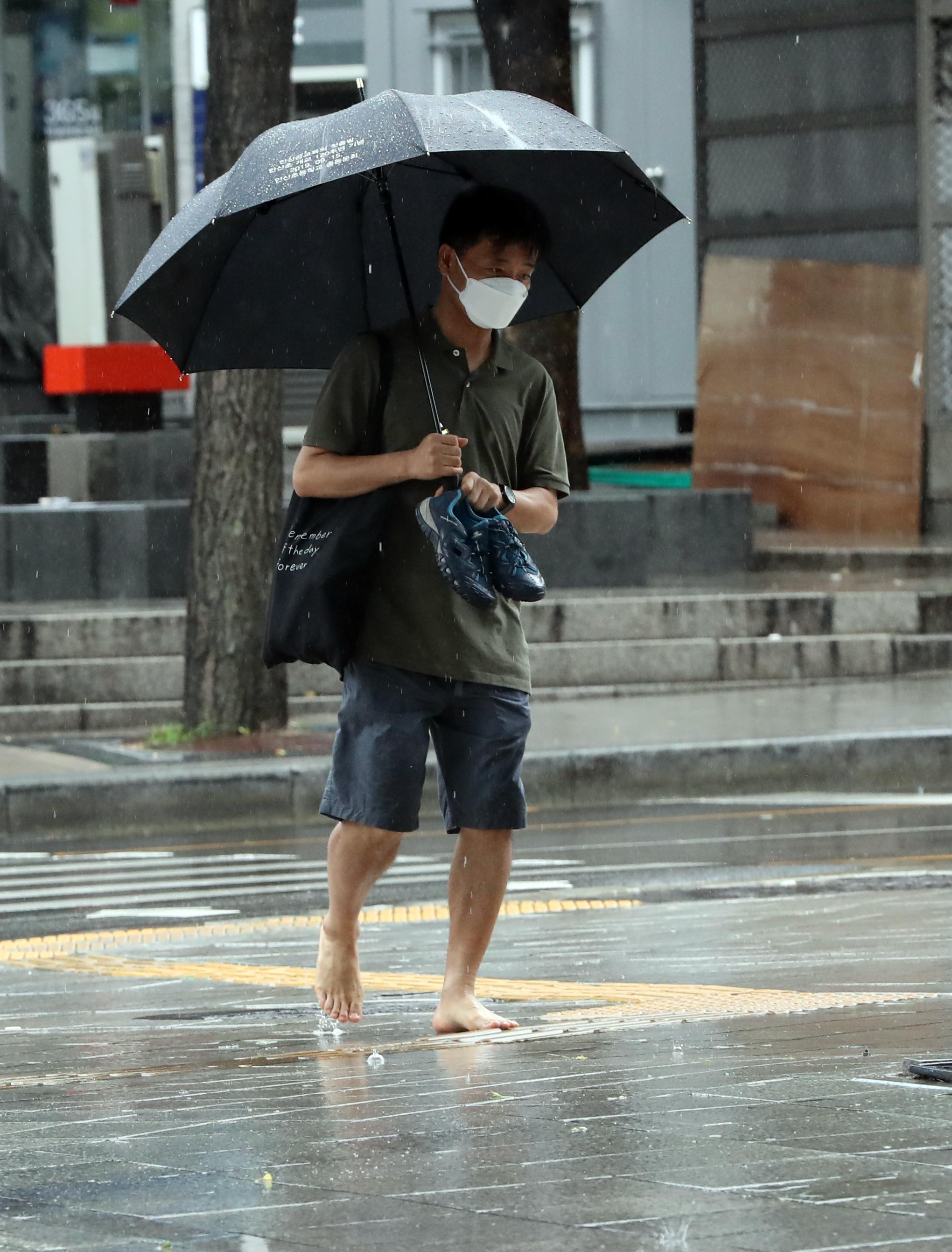 빗물에 젖은 신발 들고 맨발로 걷는 시민