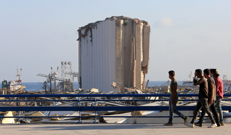 A group of men walk past the site of Tuesday's blast in the port area of Beirut, Lebanon, on August 6, 2020.