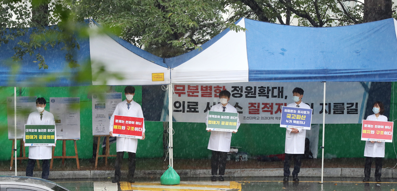 Trainee doctors stand outside a hospital in Gwanju holding signs in protest of the South Korean government's medical workforce reform plan on August 7,2020.
