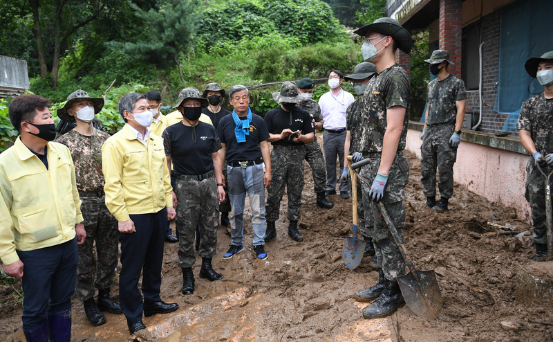 Defense Minister Jeong Kyeong-doo and other officials speak to soldier aiding recovery work in Anseong, Gyeonggi Province, after heavy rains in the region.