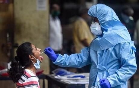 A medical worker in India conducts a throat swab on a woman at a COVID-19 testing center.