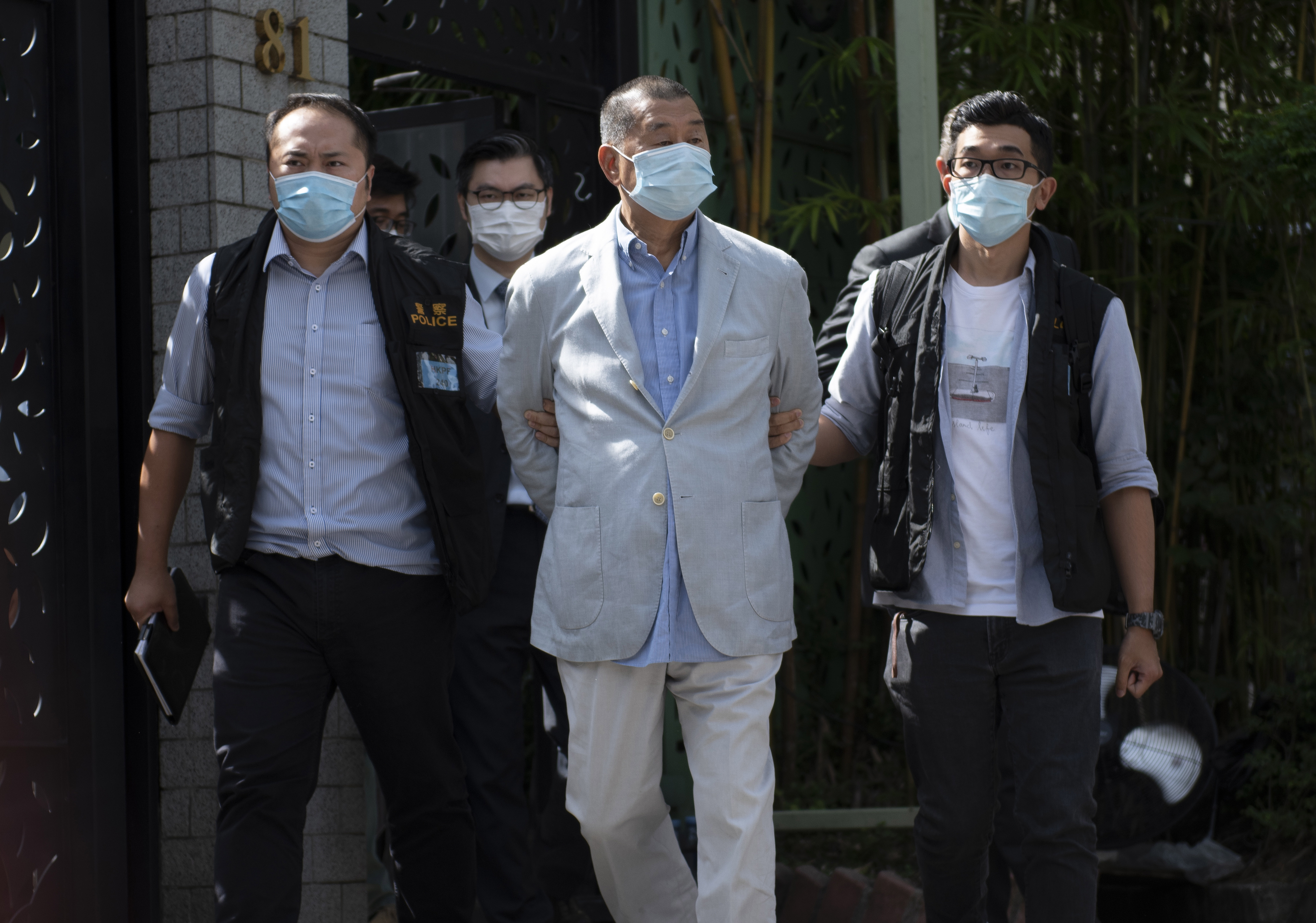 Hong Kong police escort Jimmy Lai (C), media tycoon and founder of Apple Daily, after he was arrested at his home in Hong Kong on August 10, 2020.