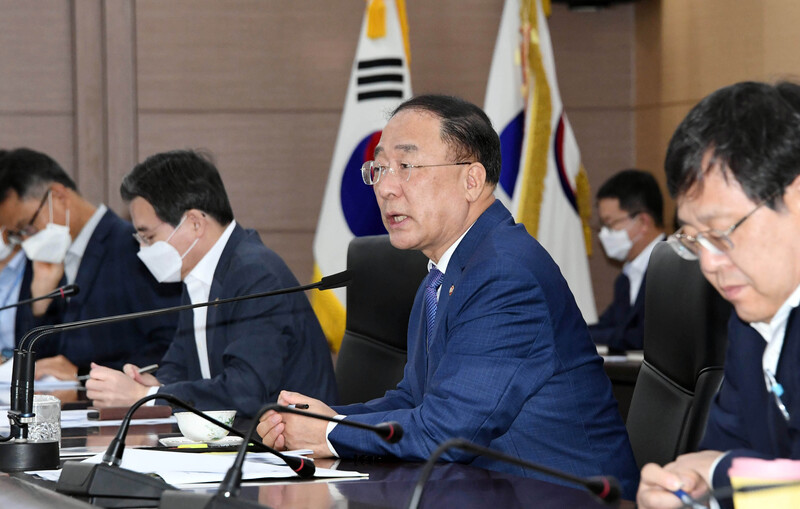 Finance Minister Hong Nam-ki (C) calls on government officials to tap into relief funds to assist people suffering from heavy rain damage in the central and southern regions during a meeting at the Government Complex in Sejong on August 10, 2020.