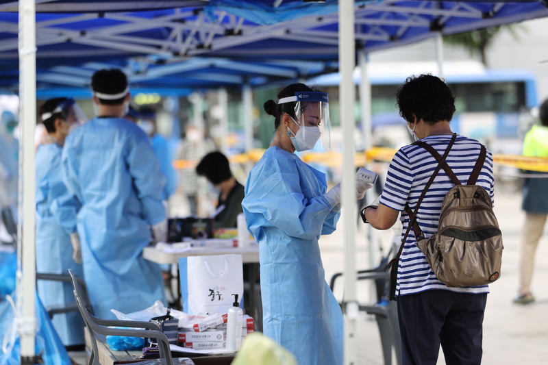 Medical workers help a woman at a makeshift coronavirus testing center set up in the Namdaemun Market in Seoul. A string of COVID-19 cases at the market have been traced to a cluster of infections from a church in Goyang, Gyeonggi Province.