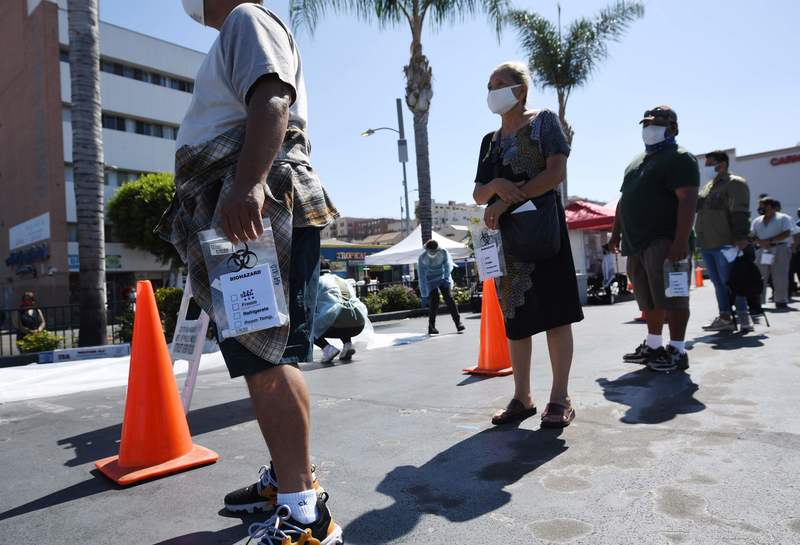 People wait in line at a walk-up coronavirus testing site in Los Angeles, California, on August 10, 2020.