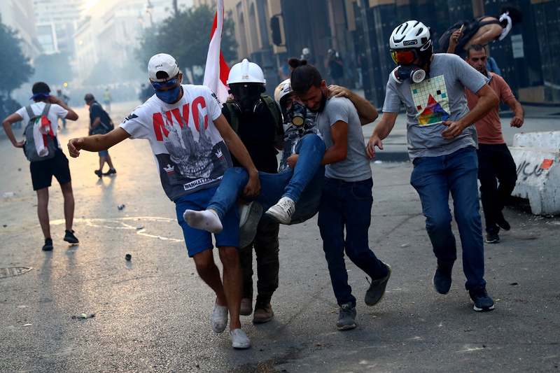 Demonstrators carry an injured man during anti-government protests ignited by a massive explosion in Beirut, Lebanon.