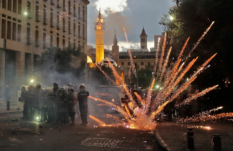 Firecrackers explode in front of riot police amid clashes with anti-government protesters in central Beirut on August 10, 2020.