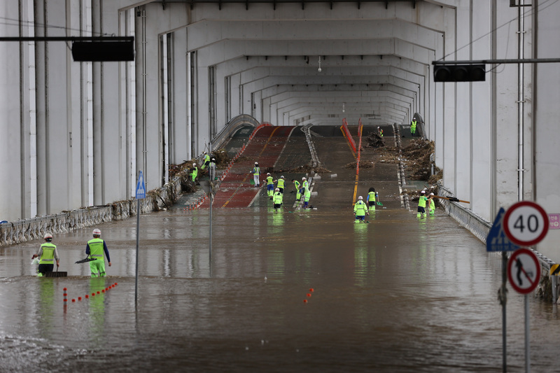 Workers from Seoul's Yongsan District attempt to clear debris as sections of the Jamsu Bridge remain flooded on August 9, 2020.