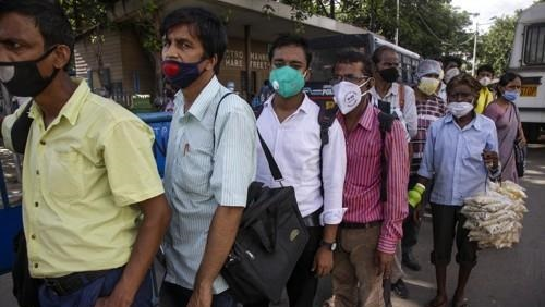 Residents in Kolkata wear masks while waiting for a bus.