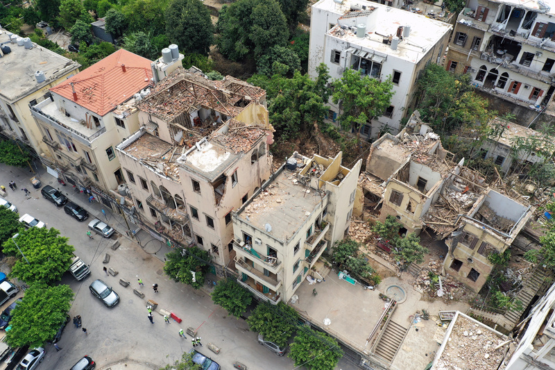 People walk past damaged buildings in the aftermath of a massive explosion in Beirut, Lebanon.