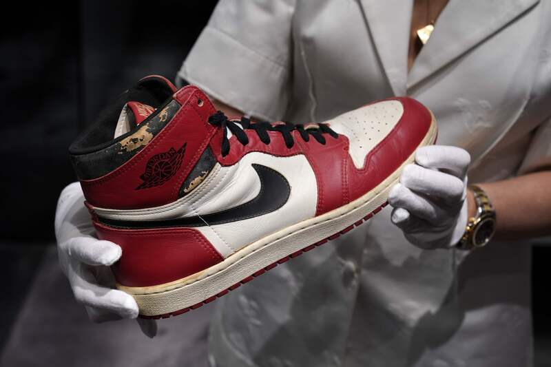 An official of Christie's New York auction house holds a Nike Air Jordan 1 sneaker, worn by basketball superstar Michael Jordan, which sold for a record $615,000.