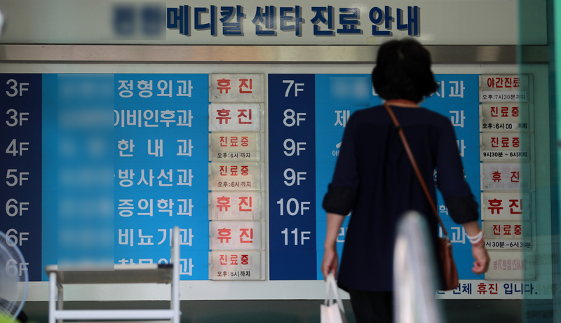 A woman stares at a board in the lobby of a medical building that shows many clinics are closed as doctors launch a one-day strike on August 14, 2020, against the South Korean government's medical reform plan.